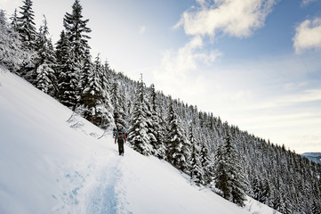 Low angle view of man hiking on snow covered mountain against sky
