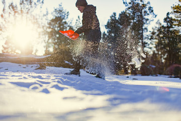 Young woman shoveling snow outdoors
