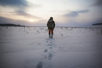 Rear view of man walking on snow covered field against sky