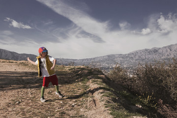 Boy playing on field against mountains and sky