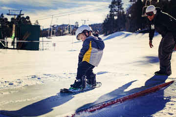 Father assisting daughter in snowboarding on sunny day