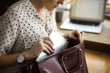 Midsection of woman putting tablet computer in purse at home office