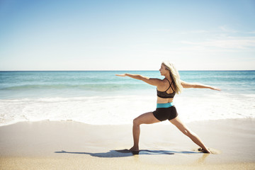 Rear view of determined woman practicing yoga in Warrior 2 pose on Delray beach