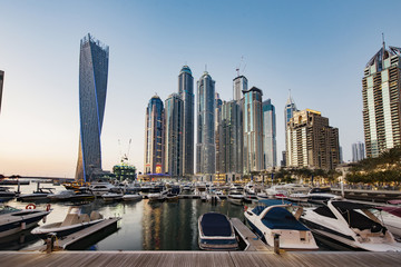 Boats moored at harbor against skyscrapers