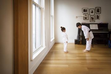 Siblings practicing karate in brightly lit home