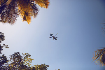 Low angle view of helicopter flying in blue sky