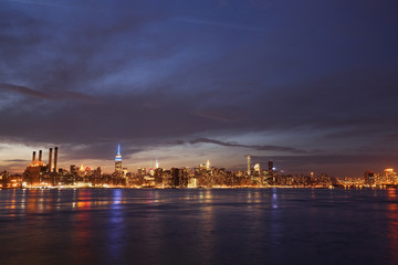 Scenic view of river and illuminated cityscape against cloudy sky at night