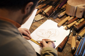 Male craftsperson drawing on paper in workshop