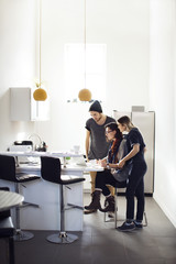Creative people looking at laptop in cafeteria during coffee break