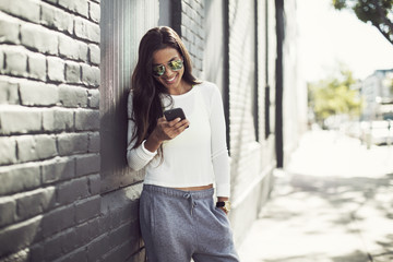 Smiling woman using phone while standing against wall on sunny day