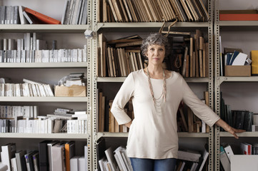 Portrait of confident interior designer standing against shelves in office
