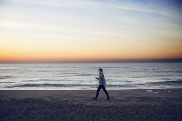 Full length of woman walking at beach against sky