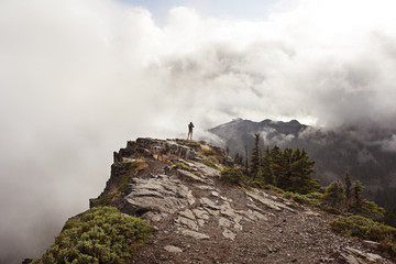 Rear view of man photographing while standing on mountain against cloudy sky