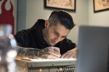 Male tattoo artist drawing design on paper at studio