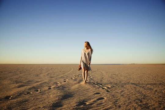 Carefree woman walking on beach against clear blue sky during sunset