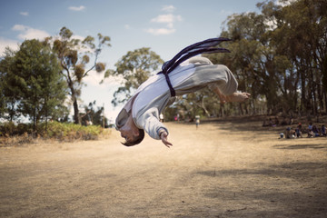 Male martial artist performing back flip on dirt road