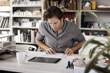 Male interior designer using tablet computer while analyzing documents at desk in office