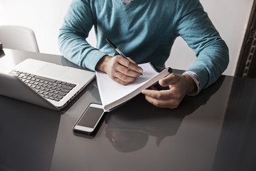 Midsection of man writing on book by laptop at table in office