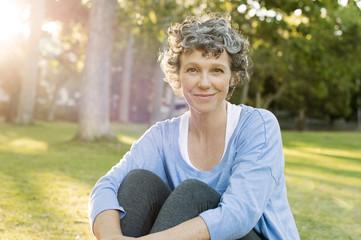 Portrait of mature woman sitting on field