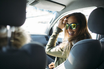 Smiling young woman wearing sunglasses sitting in car during winter
