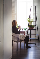 Woman drinking coffee while sitting on chair at home