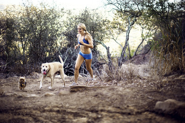 Young woman running with dogs in forest