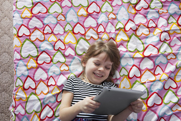 Overhead view of smiling girl holding digital tablet and lying on bed