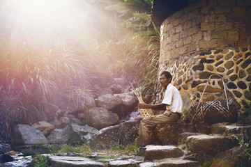 Senior man weaving basket while sitting outside home