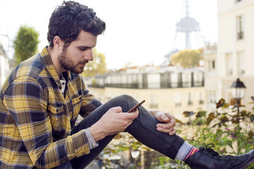 Young man using smart phone against buildings