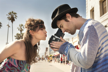 Side view of woman puckering lips while man photographing through vintage camera on sidewalk
