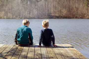 Rear view of boys sitting on pier over lake