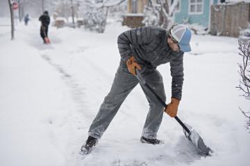 A man removing snow on sidewalk