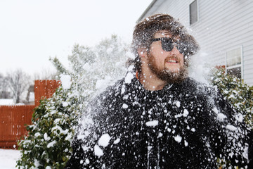 Snow falling on young man standing outside house