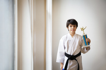 Portrait of boy holding award and standing at home