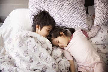 Siblings sleeping on bed