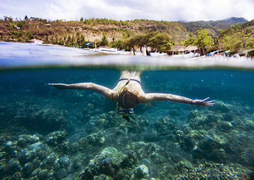 Woman snorkeling in sea against mountain