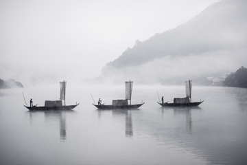 People rowing traditional boats in lake