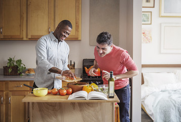 Happy multi-ethnic gay couple preparing food in kitchen at home