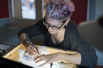 Female tattoo artist drawing on paper in studio