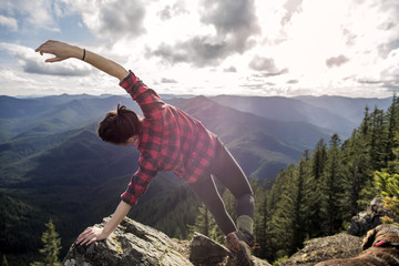 Woman bending with arms outstretched on rock at mountain cliff against sky
