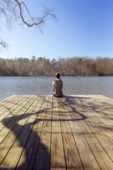 Rear view of teenage girl sitting at the edge of pier over lake against clear blue sky