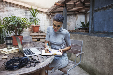 Woman writing in diary outdoors