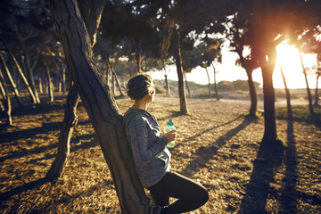 Tired jogger holding bottle while leaning on tree in park at morning