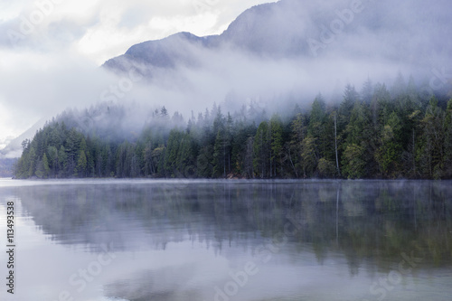 Fotomurales Foggy morning at the lake. Forest reflection. Forest fog. Cloudy weather. Cloudy morning. Forest and mountain. Vancouver nature. Pacific North West. Nature. Nature park. Early morning. Sunrise.