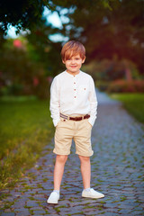 portrait of cute young fashionable boy posing outdoors