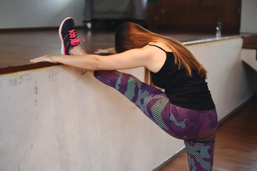 Athlete young woman doing exercise at gym. Indoors.