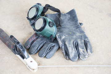 Used welding equipment such as glove and goggles and etc.On cement floor background