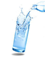 Pouring water from bottle into glass with splashing. Isolated on white background.