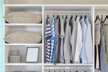 modern closet with row of cloths hanging in white wardrobe