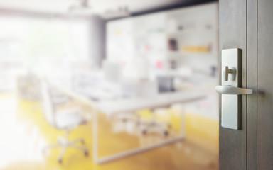 opened wooden door to blurred interior of modern working room with yellow floor